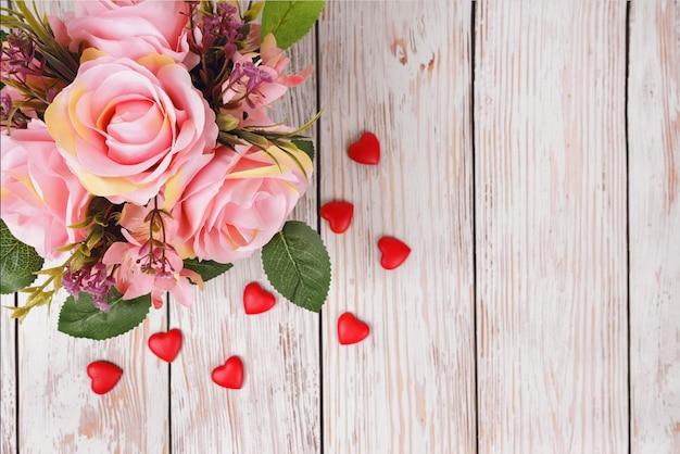 木製のピンクのサインとピンクのバラの美しいロマンチックな花束私は白いレンガの壁の背景にあなたを愛しています。バレンタインデー、結婚式のコンセプト。