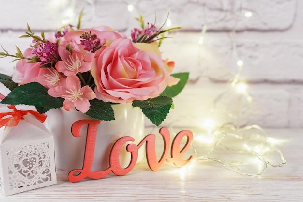 輝く光と白いレンガの壁の背景に木製のピンクの言葉の愛と透かし彫りのギフトボックスとピンクのバラの美しいロマンチックな花束。バレンタインデー、結婚式のコンセプト。