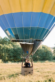 Beautiful romantic caucasian couple in love hugging in the basket of colorful hot air balloon during summer sunset, celebrating engagement or wedding anniversary