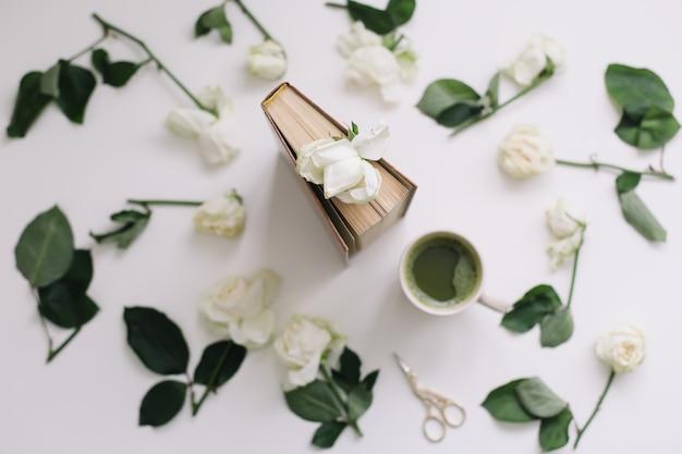 白い背景の上の抹茶緑茶とバラの花のカップと美しいロマンチックな構成