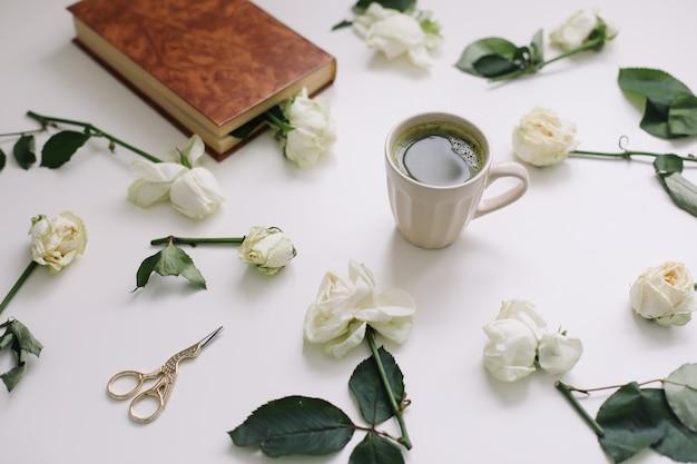 Красивая романтическая композиция с чашкой зеленого чая матча и розовыми цветами на белом фоне