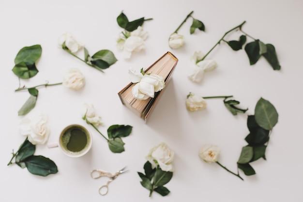 Красивая романтическая композиция с чашкой зеленого чая матча и розовыми цветами на белой поверхности