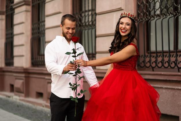 아름 다운 로맨틱 커플. 빨간 드레스와 빨간 장미 거리에 걷는 흰 셔츠에 잘 생긴 남자와 왕관에 매력적인 젊은 여자. 해피 세인트 발렌타인 데이. 임신과 결혼 개념.
