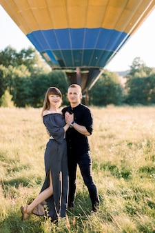 Beautiful romantic couple in black clothes, hugging at beautiful summer green meadow with hot yellow air balloon