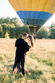 Beautiful romantic couple in black clothes, hugging and dancing at beautiful summer green meadow with hot yellow air balloon