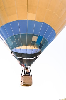 Beautiful romantic couple hugging in the basket of hot air balloon, flying in summer sunny evening