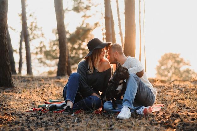 아름다운 낭만적인 커플은 일몰의 가을 숲에서 야외에서 개 프렌치 불독과 즐거운 시간을 보내고 있습니다.