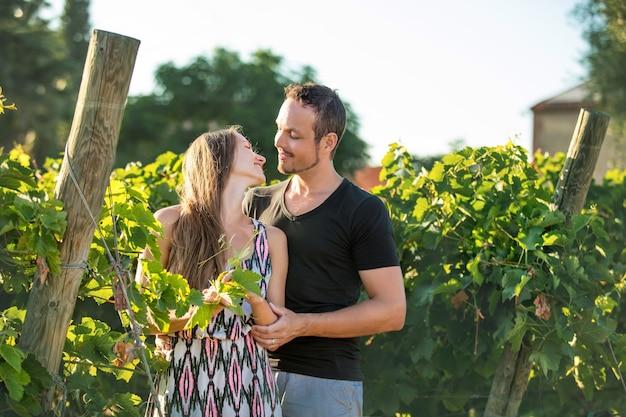 一緒にブドウ園を歩く美しいロマンチックなカップルの男性と女性の若い大人