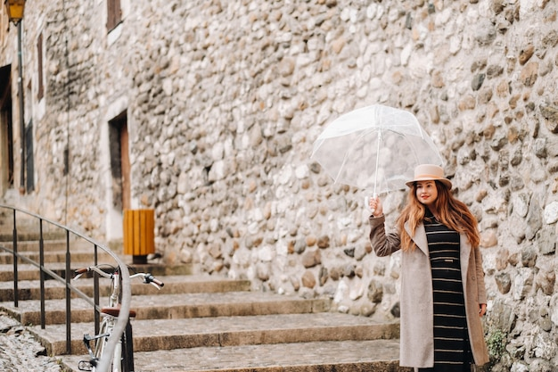 Beautiful romantic girl in a coat and hat with a transparent umbrella in annecy. france. the girl in the hat in france.