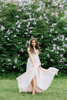 Beautiful romantic girl in a pink delicate dress flying in the wind stands in the spring near a lilac bush