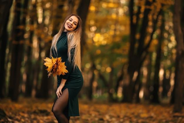 秋の公園でカエデの葉の花束を持つ美しいロマンチックな女の子