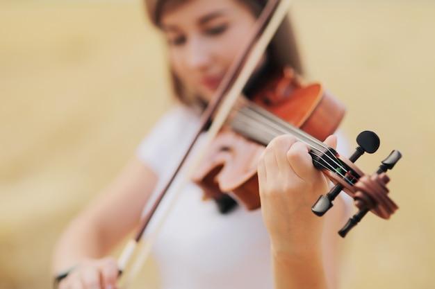 Красивая романтическая девушка с распущенными волосами играет на скрипке в поле после сбора урожая
