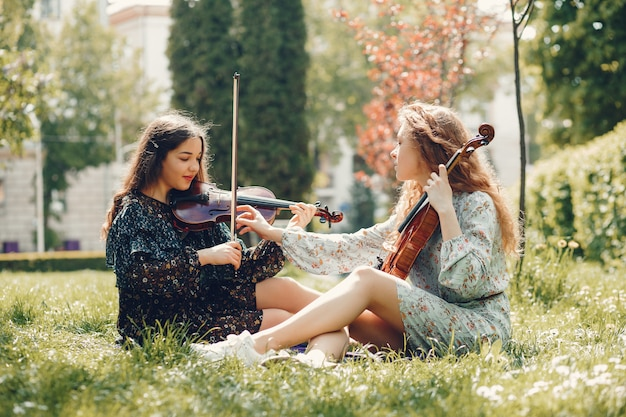 Beautiful and romantic girls in a park with a violin