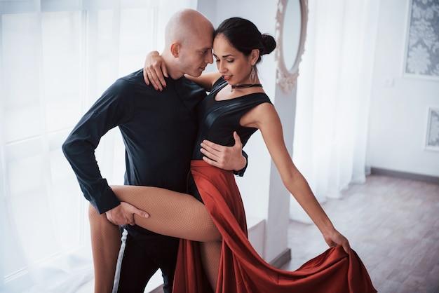 Bella posa romantica. giovane donna graziosa in vestiti rossi e neri che ballano con il ragazzo calvo nella stanza bianca