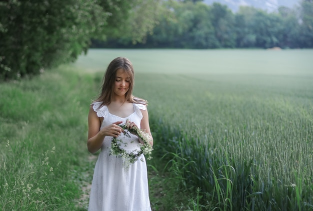 Beautiful romantic preteen girl making green and white fresh flowers head wreath outdoors at green field.