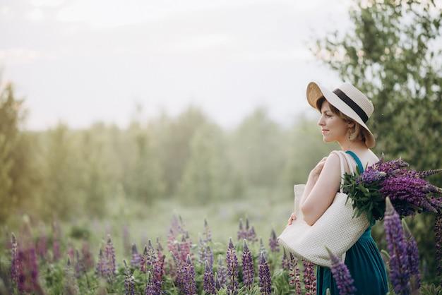 日の出のルピナスの紫色の花の花束を持つフィールドで帽子とドレスの金髪の美しいロマンチックな女性。