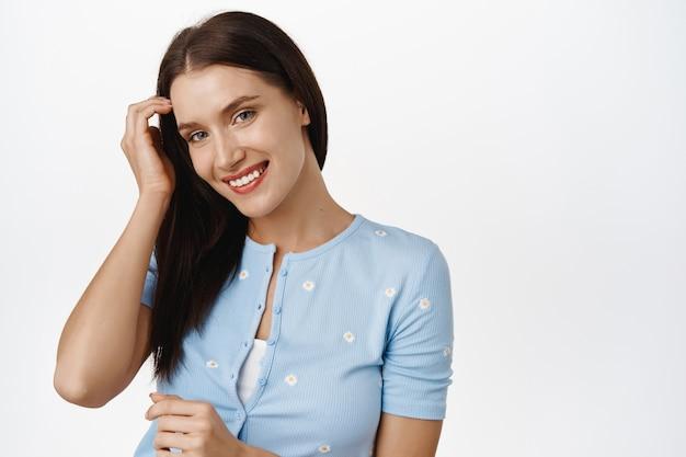 トレンディなブラウスを着た美しいロマンチックな女性、耳の後ろに髪を押し込み、軽薄に笑って笑い、コケティッシュでキュートな顔をして、白の上に立っています。