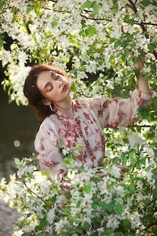 아름 다운 낭만적인 여자 개화 사과 나무의 가지에 서 있다. 꽃 사과 나무에 봄 초상화 소녀