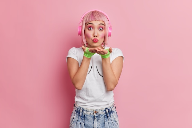 Beautiful romantic young asian woman blows air kiss at camera has pink bob hair wears stereo headphones on ears listens music from playlist dressed in sport gloves t shirt and jeans poses indoor.