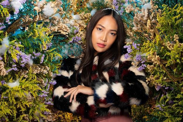 부시 대통령은 다양 한 배경 신선 하 고 말린 식물에 포즈에 검은 모피 옷감에 아름 다운 로맨틱 젊은 아시아 여자. 가을 겨울 눈 향수, 화장품 개념의 영감.