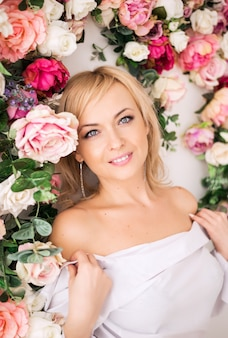 Beautiful romantic young blonde woman with natural makeup posing of flowers, flower wall in pink. perfume and cosmetic concept