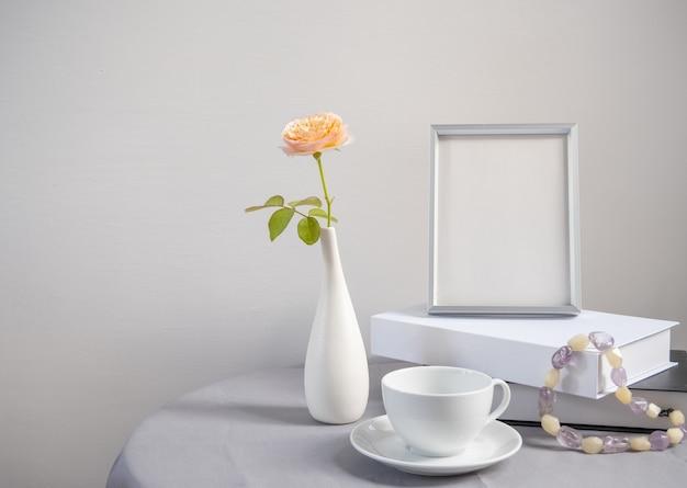 Красивый цветок розы в белой вазе с книгой в серебряной рамке и чашкой кофе на столе из льняной ткани в интерьере комнаты
