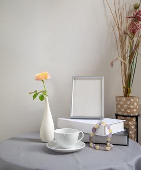 Красивый цветок розы в белой вазе с книгой в серебряной рамке и кофейной чашкой на столе из льняной ткани