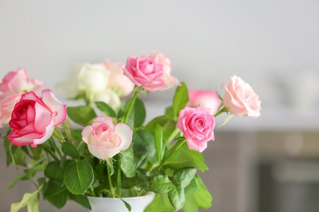 Красивые розовые цветы в вазе на размытом