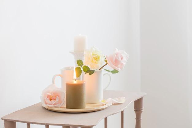 Красивые розы и зажженные свечи на белой стене