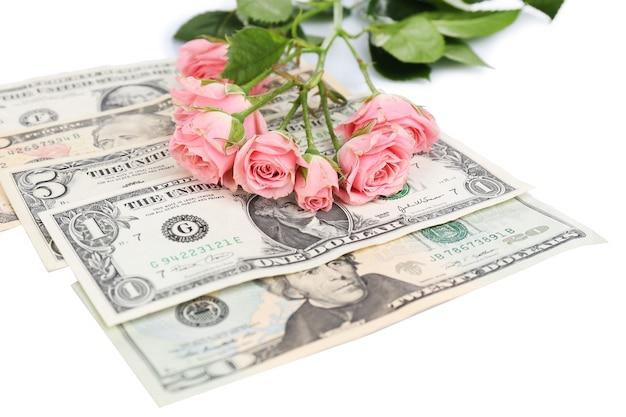 白で隔離された美しいバラとお金