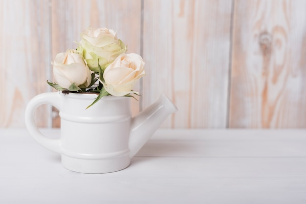 Beautiful roses in the ceramic small watering can on wooden table