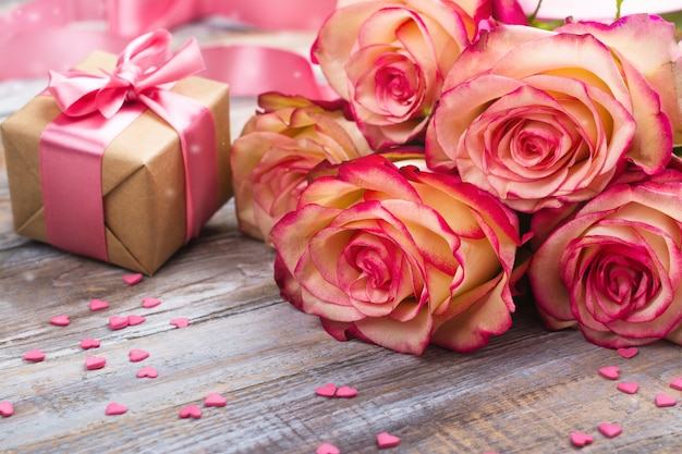 Beautiful roses and gift box on wooden background. valentines day or mothers day greeting card