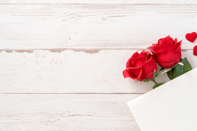 Beautiful roses and hearts shape with white empty card isolated on a bright wooden table, copy space, flat lay, top view, mock up