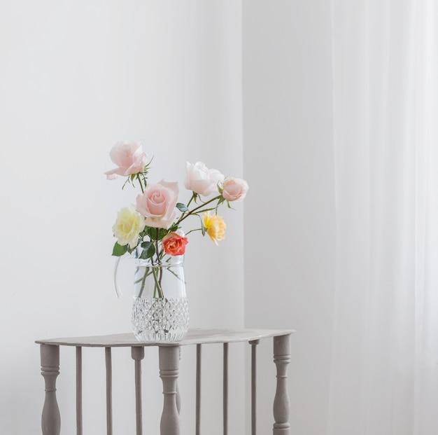 Красивые розы в стеклянном кувшине на белом фоне