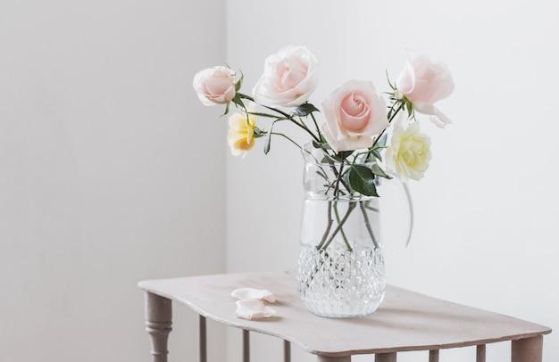 Красивые розы в стеклянном кувшине на белой поверхности