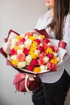 Красивые розы в руках. весна, лето, цветы, цветовая концепция. доставка цветов