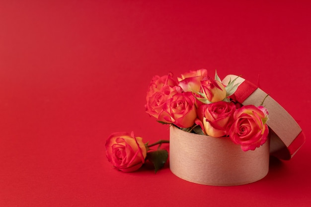 赤い表面、テキストのためのスペースの木製ギフトボックスの美しいバラ。ホリデーグリーティングカード