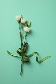 ミントの背景に緑のリボンと美しいバラ
