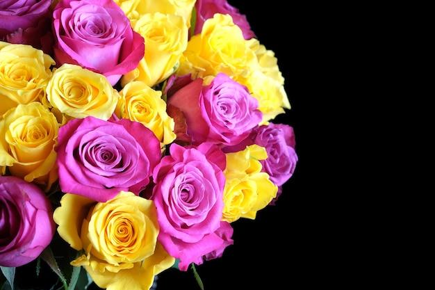 검은 배경 근접 촬영에 고립 된 사진의 왼쪽에 분홍색과 uellow 장미 꽃의 아름 다운 라운드 꽃다발