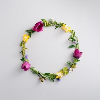 Красивая круглая рамка из цветного цветка. круг из свежих цветов и листьев на светло-сером фоне. вид сверху, копия пространства.