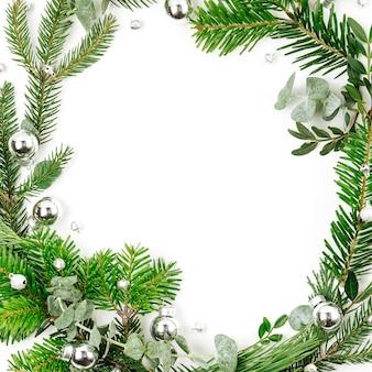 白い背景の上のクリスマスの装飾とモミと松の枝の美しい丸いフレーム。クリスマスのコンセプト。フラットレイ、上面図
