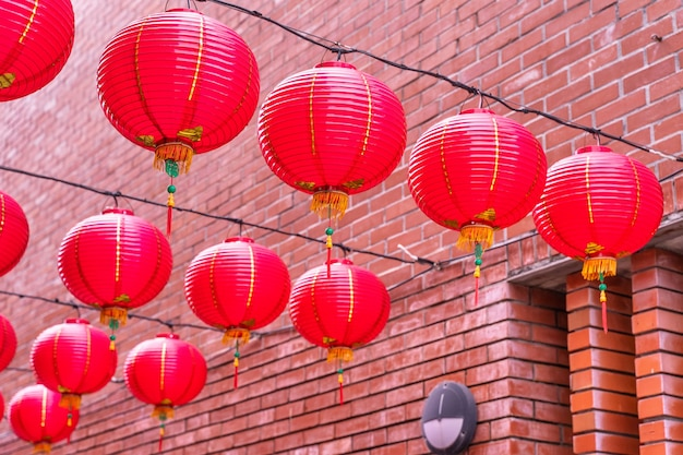 Beautiful round red lantern hanging on old traditional street, concept of chinese lunar new year festival, close up. the undering word means blessing.