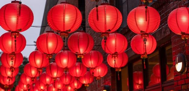 중국 음력 새해 축제의 개념인 오래된 전통 거리에 매달려 있는 아름다운 둥근 빨간 등이 닫힙니다. 아래 단어는 축복을 의미합니다.