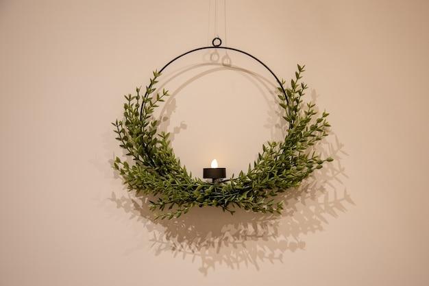 明るい壁に美しい丸いリングのクリスマス燭台の花輪。