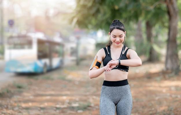 Beautiful runner using smart watch to monitor her performance
