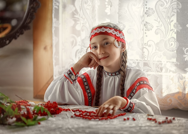 Beautiful russian girl smiles sitting at the table