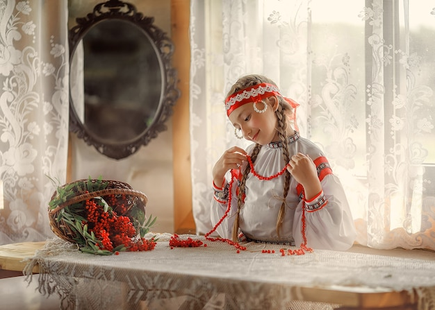 Beautiful russian girl tries on a necklace of rowan berries