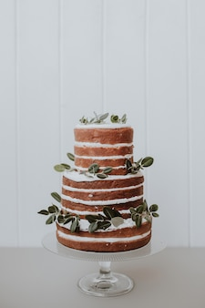 Beautiful rustic wedding cake decorated with eucalyptus on white wooden background