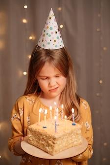 Красивая грустная девушка с праздничным тортом. традиция загадывать желание и задуть костер на вечеринке. день отдыха.
