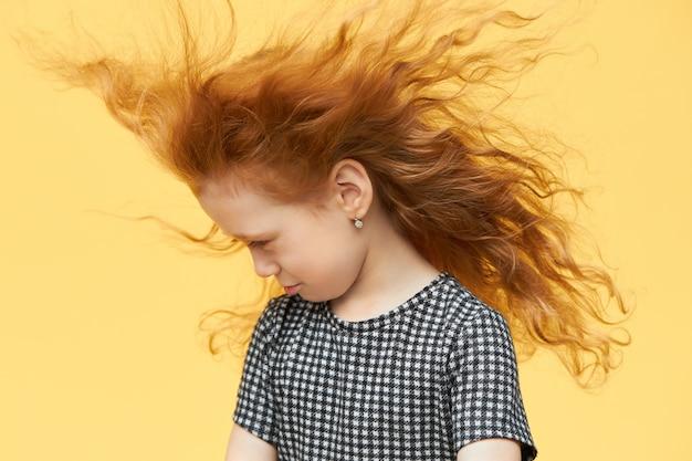 Красивая грустная маленькая девочка в клетчатом платье, глядя вниз